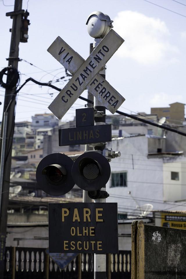 Matéria especial Ferrovias Mineiras - Conselheiro Lafaiete. Linha de trem. Passagem de nível. Sinalização. Placa de Pare olhe escute.